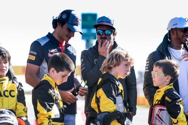 Circuit de Catalunya, Barcelona, Spain. Thursday 11 May 2017. Carlos Sainz Jr, Toro Rosso, Fernando Alonso, McLaren, and Lewis Hamilton, Mercedes AMG, with some junior Kart racers. World Copyright: Dom Romney/LAT Images ref: Digital Image GT2R9786