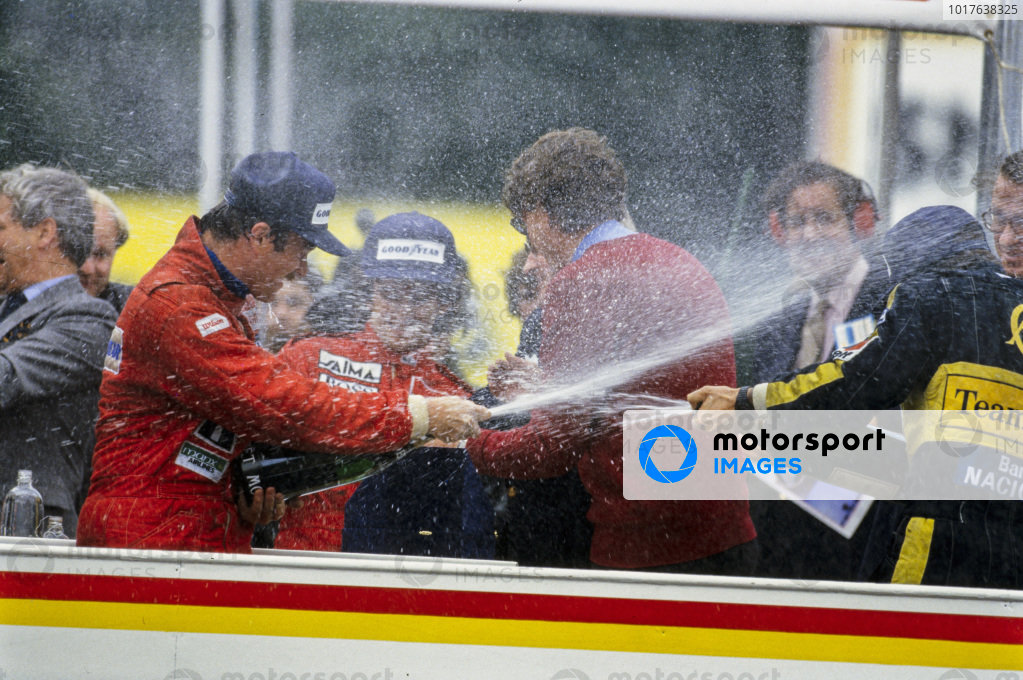 Nigel Mansell, 1st position, sprays champagne on the podium with Ayrton Senna, 2nd position. Alain Prost, 4th position, is also present as he secured his first world championship in this race.