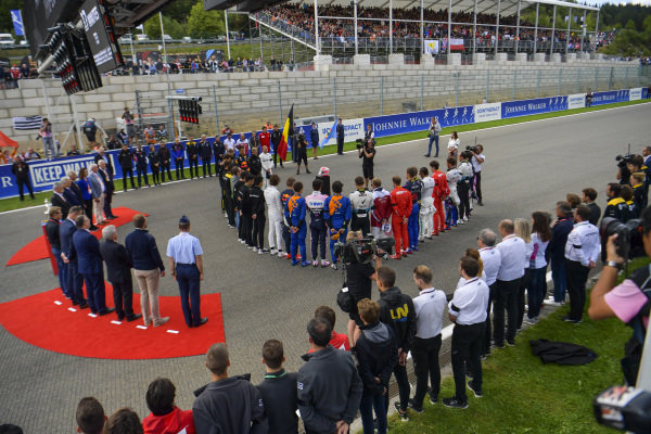 The drivers, team members, officials and staff gather on the grid to pay their respects to Anthoine Hubert who tragically lost his life the day before in the F2 race