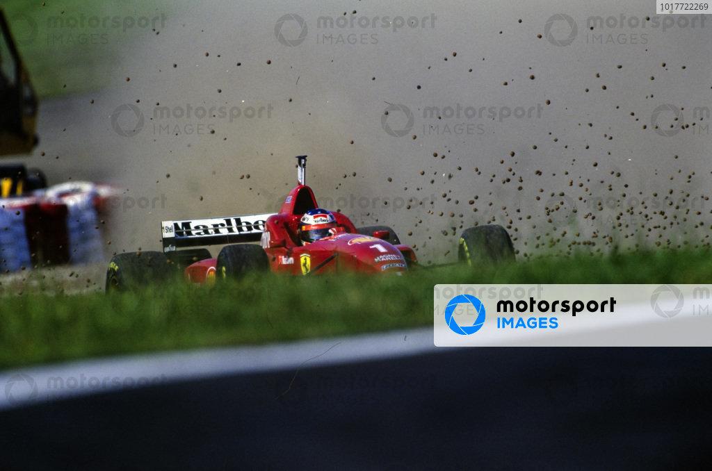 Michael Schumacher, Ferrari F310, runs wide and kicks up gravel.