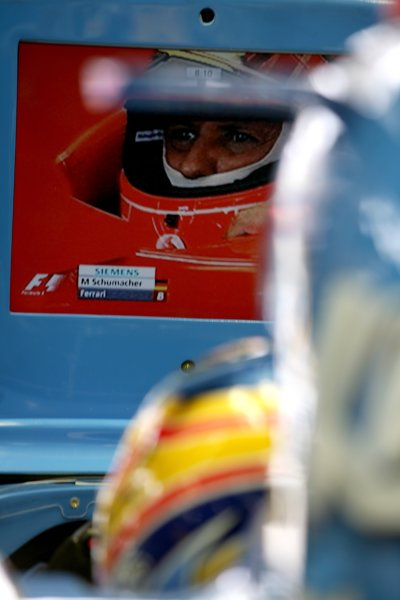 2006 Brazilian Grand Prix - Friday Practice Interlagos, Sao Paulo, Brazil. 19th - 22nd October 2006. Fernando Alonso, Renault R26, watches championship rival Michael Schumacher, Ferrari 248F1, on the television screen, atmosphere. World Copyright: Charles Coates/LAT Photographic ref: Digital Image ZK5Y8849