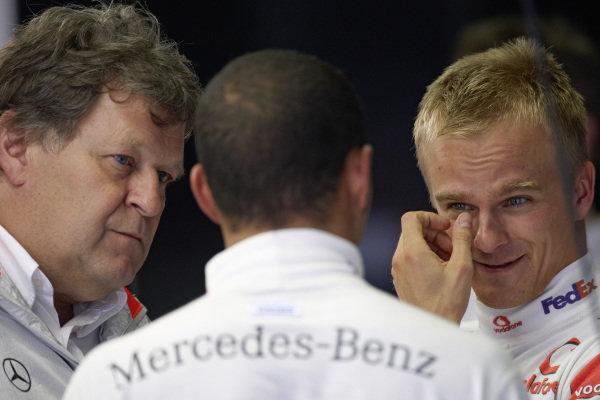 Mercedes Motorsport director Norbert Haug and Heikki Kovalainen speak with Lewis Hamilton.