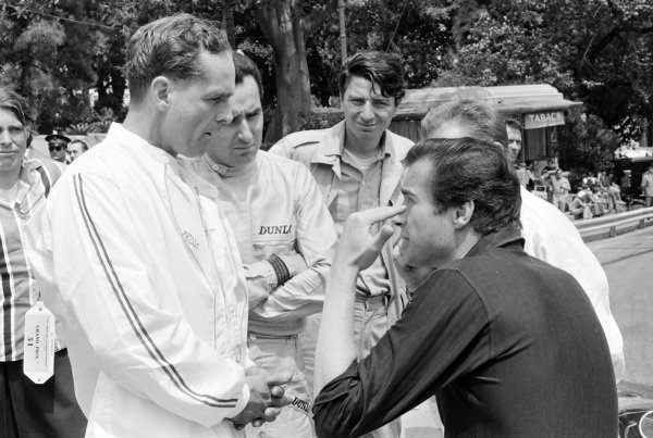 Phil Hill and Lorenzo Bandini talk to Hollywood director John Frankenheimer, who was making the film Grand Prix.