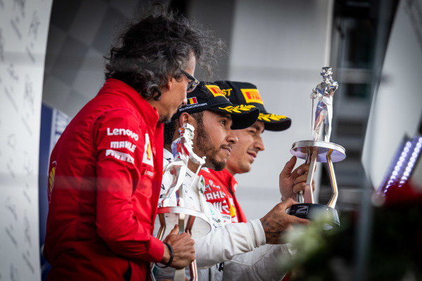 Laurent Mekies, Sporting Director, Ferrari, Lewis Hamilton, Mercedes AMG F1, 2nd position, and Charles Leclerc, Ferrari, 1st position, on the podium