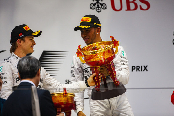 Lewis Hamilton, 1st position, celebrates on the podium alongside Nico Rosberg, 2nd position.