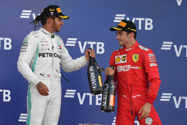 Lewis Hamilton, Mercedes AMG F1, 1st position, and Charles Leclerc, Ferrari, 3rd position, celebrate with Champagne on the podium