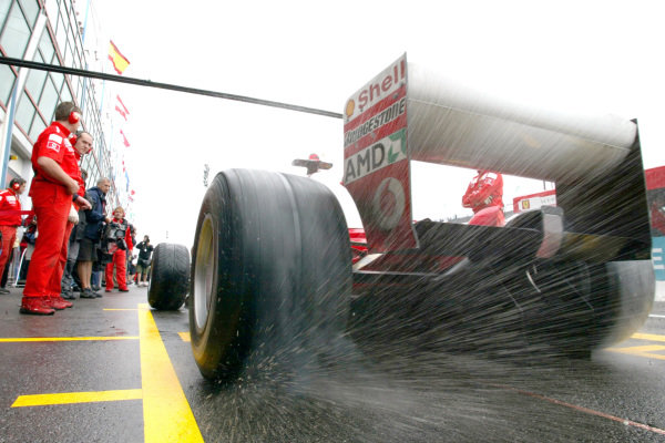 Water sprays from the rear tyres of Michael Schumacher's Ferrari F2003-GA as he leaves his pit box.