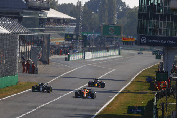 Lando Norris, McLaren MCL35M, leads Max Verstappen, Red Bull Racing RB16B, and Sir Lewis Hamilton, Mercedes W12