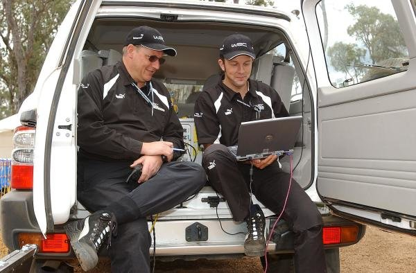 WRC official Data Engineers work on a laptop from the back of their van.