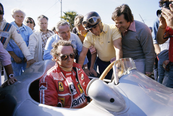 Niki Lauda takes a seat in a Mercedes Grand Prix car from 1954. The driver of the car at that time was Juan Manuel Fangio, five times F1 World Champion (in the background with helmet on).