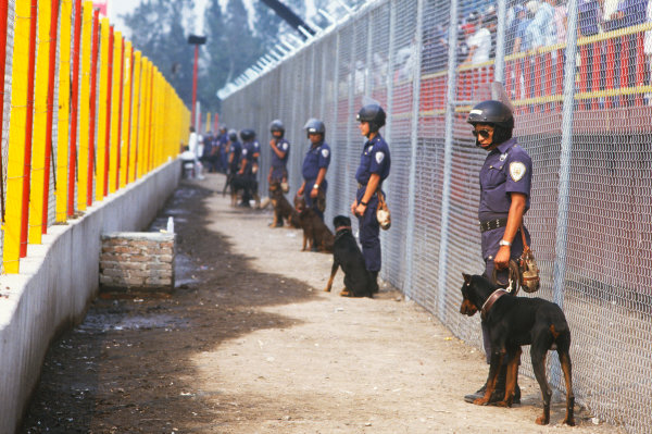 1986 Mexican Grand Prix  Mexico City, Mexico. 9-12th October 1986.  Police with dogs guard the fence in front of a grandstand.  Ref: 86MEX41. World copyright: LAT Photographic