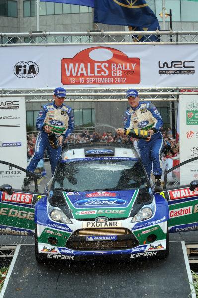 Jari-Matti Latvala (FIN) and Miikka Anttila (FIN), Ford Fiesta RS WRC celebrate victory on the podium. FIA World Rally Championship, Rd10, Wales Rally GB, Day Three, Cardiff, Wales, 16 September 2012.