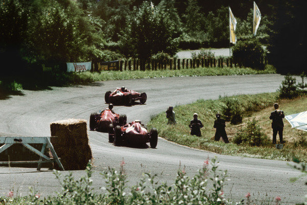 Nurburgring, Germany. 2-4 August 1957. Mike Hawthorn (Lancia-Ferrari D50) leads Juan Manuel Fangio (Maserati 250F) and Peter Collins (Lancia-Ferrari D50) in the closing laps of the race. Fangio passed Hawthorn to win his greatest race. Ref: 57 GER 19 World Copyright - Tony Smythe/ LAT Photographic