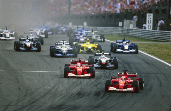 Michael Schumacher, Ferrari F2001, leads Rubens Barrichello, Ferrari F2001, and David Coulthard, McLaren MP4-16 Mercedes, into the first corner at the start.