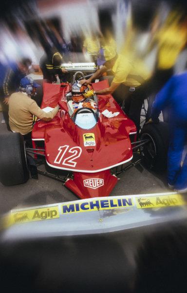 A mechanic cleans Gilles Villeneuve's helmet as he waits in his Ferrari 312T4.