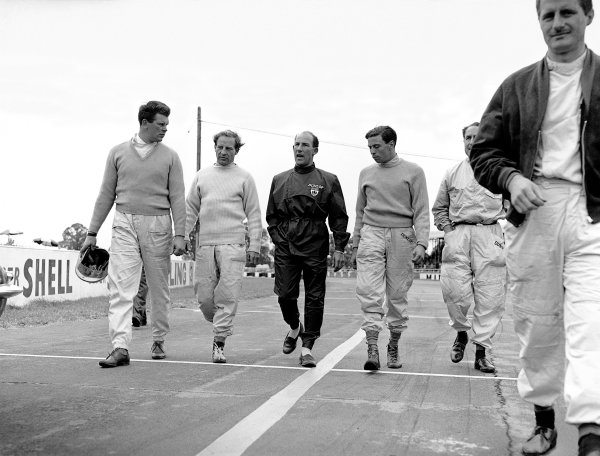 Silverstone, England. 8th July 1961. L to R: Tim Parnell, Innes Ireland, Stirling Moss, Jim Clark, Jack Fairman and Lucien Bianchi walk to the start line, portrait. Stirling Moss won the race. World Copyright: LAT Photographic. Ref: Autocar Glass Plate C62862.