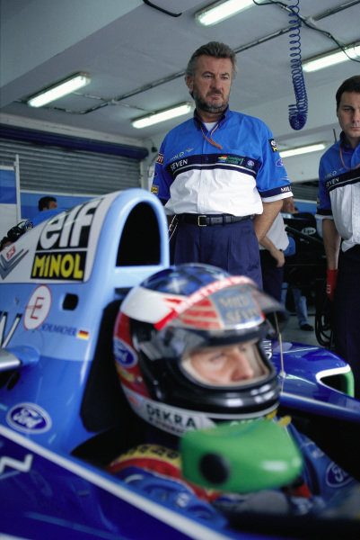 Michael Schumacher's manager Willi Weber standing behind his driver.