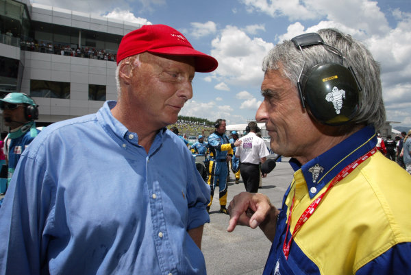 2003 Malaysian Grand Prix. Sepang, Kuala Lumpur, Malaysia.21-23 March 2003.Niki Lauda has a chat with Michelin Director of Worldwide Racing Piere Dupasquier. World Copyright - Steve Etherington/LAT Photographic ref: Digital Image Only