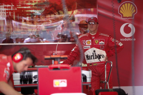 Michael Schumacher stands at the back of the garage.