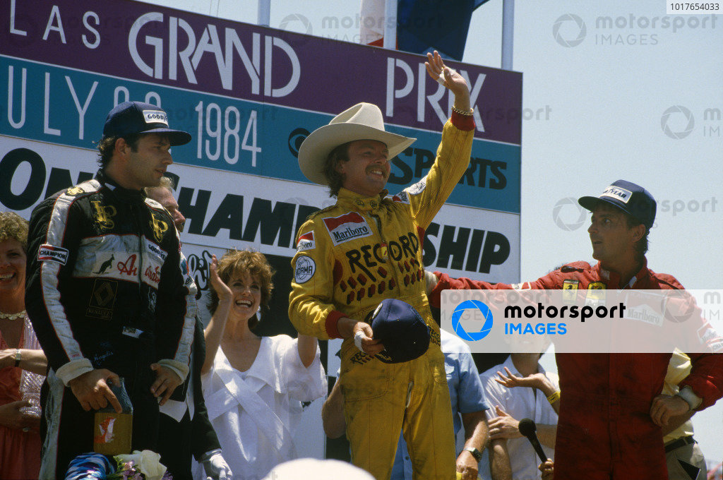 Keke Rosberg, 1st position, wears a stetson on the podium. René Arnoux, 2nd position, and Elio de Angelis, 3rd position, are also on the podium. Actress Linda Gray, who played Sue Ellen Ewing in Dallas, looks on.