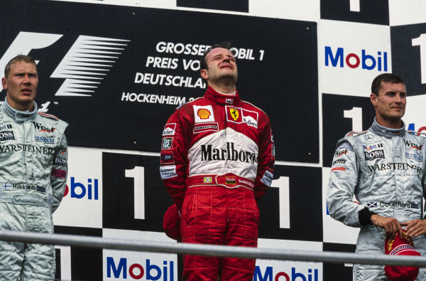 Rubens Barrichello, 1st position, cries on the podium after securing his maiden victory. Alongside are Mika Häkkinen, 2nd position, and David Coulthard, 3rd position.