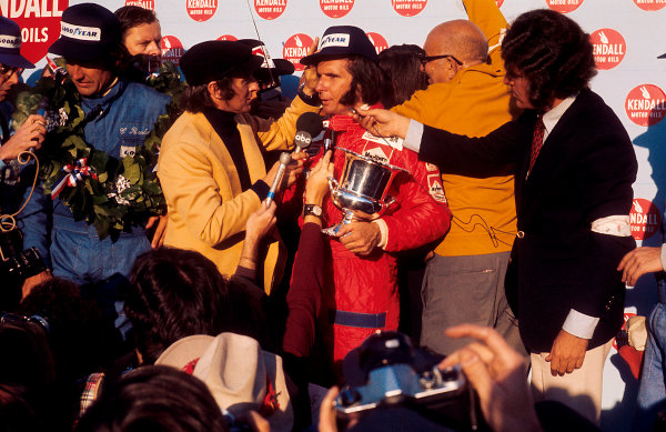 1974 United States Grand Prix Watkins Glen, New York, USA 4-6 October 1974 New drivers world champion Emerson Fittipaldi celebrates taking his second world title, here being interviewed by the outgoing champion Jackie Stewart. Race winner Carlos Reutemann (Brabham Ford) 1st position is to the left of him on the podium. Ref-74 USA 04 World Copyright - LAT Photographic