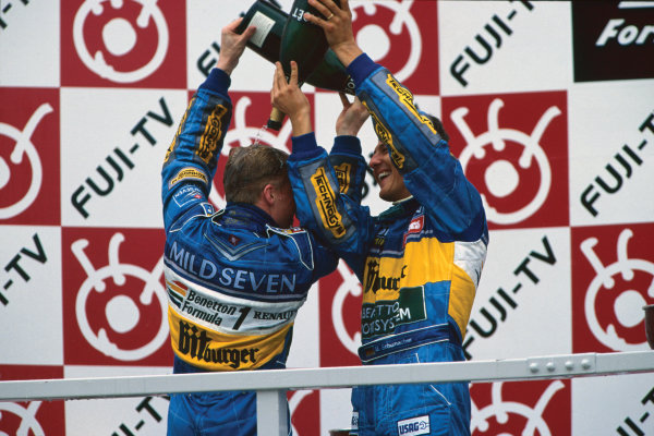 Suzuka, Japan. 27-29 October 1995. Michael Schumacher and Johnny Herbert (Benetton B195 Renault) celebrate after finishing in 1st and 3rd positions respectively, podium, portrait.  World Copyright: LAT Photographic. Ref:  95 JAP 12.
