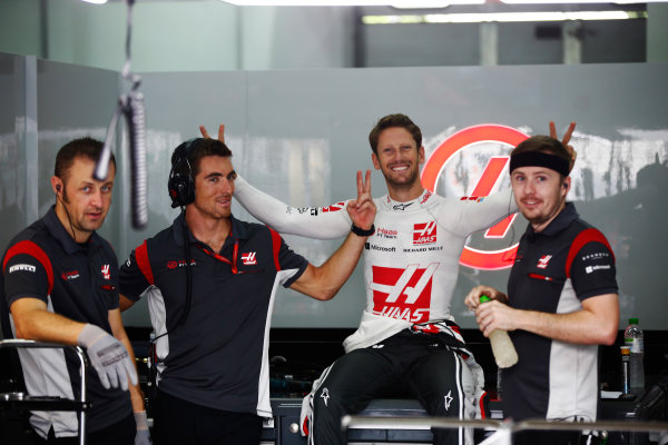 Sepang International Circuit, Sepang, Malaysia. Friday 29 September 2017. Romain Grosjean, Haas F1, jokes with mechanics during a rain delay in FP1. World Copyright: Andy Hone/LAT Images  ref: Digital Image _ONY1337