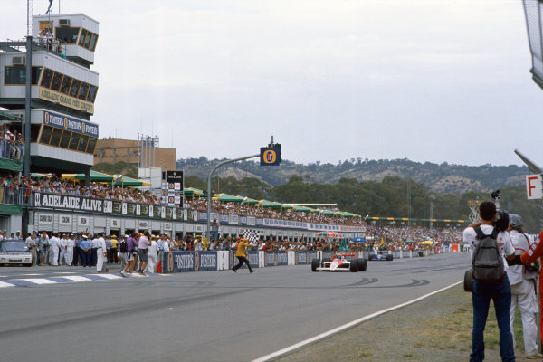 1988 Australian Grand Prix. Adelaide, Australia. 11th - 13th November 1988. Alain Prost (McLaren MP4/4-Honda), 1st position, takes the chequered flag, action.  World Copyright: LAT Photographic.  Ref:  88AUS