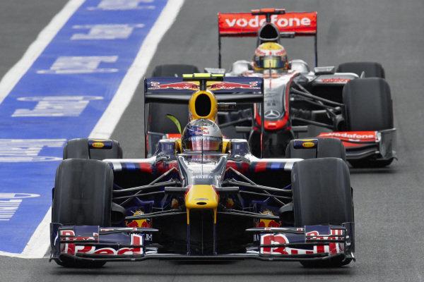 Sebastian Vettel, Red Bull RB5 Renault leads Lewis Hamilton, McLaren MP4-24 Mercedes out of the pit lane.