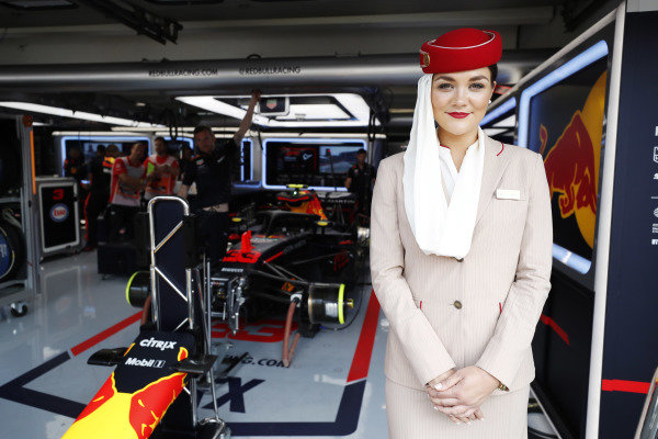 An Emirates flight attendant poses in front of the Red Bull garage, and the Max Verstappen Red Bull Racing RB14 Tag Heuer.