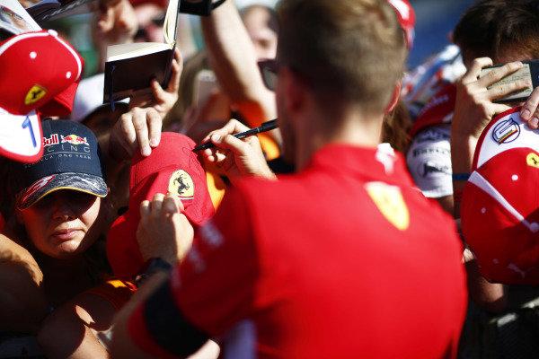 Sebastian Vettel, Ferrari, signs an autograph for a fan.
