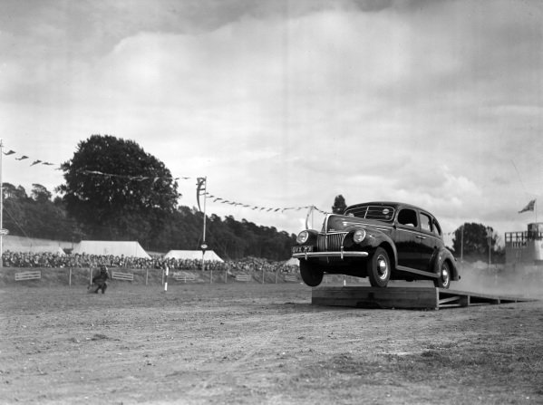 A Ford V8 jumps off a ramp as part of a display.