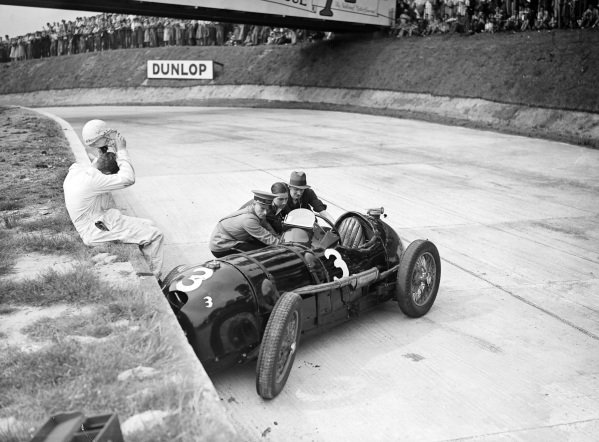 A driver sits on the wall and removes his helmet as officials work to remove his stricken car.
