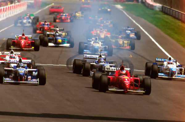 Imola, Italy.3-5 May 1996.Michael Schumacher (Ferrari F310) looks across at rival Damon Hill (Williams FW18 Renault) as they pull away from the grid at the start.Ref-96 SM 05.World Copyright - LAT Photographic