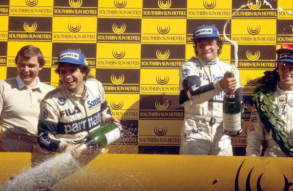 Kyalami, South Africa.13-15 October 1983.Riccardo Patrese (Brabham BT52B-BMW) 1st position, Andrea de Cesaris (Alfa Romeo) 2nd position and Nelson Piquet (Brabham BT52B-BMW) 3rd position, podium.World Copyright: LAT Photographic.