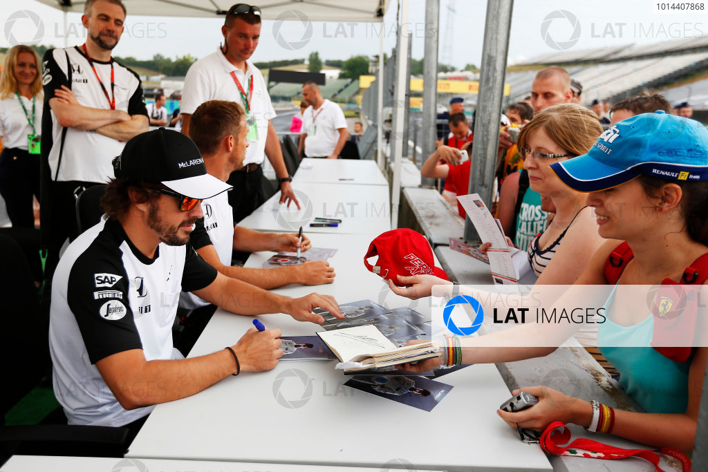 Hungaroring, Budapest, Hungary. Thursday 23 July 2015. Fernando Alonso, McLaren, and Jenson Button, McLaren, sign autographs for fans. World Copyright: Charles Coates/LAT Photographic ref: Digital Image _N7T1935