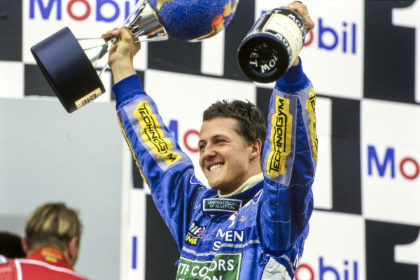 Michael Schumacher, 1st position, celebrates on the podium with his trophy and champagne.