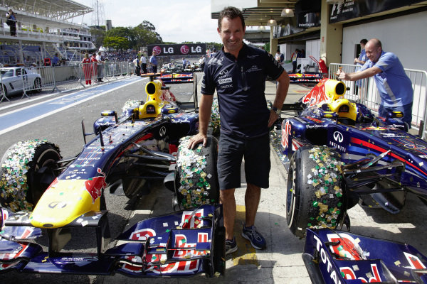 Kenny Handkammer poses between the confetti-covered Red Bull RB7 Renault cars in Parc Ferme.