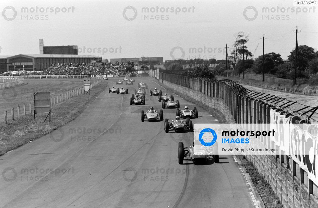 Jim Clark, Lotus 25 Climax, leads John Surtees, Lola 4 Climax, as Dan Gurney, Porsche 804, and Bruce McLaren, Cooper T60 Climax, battle at the start.