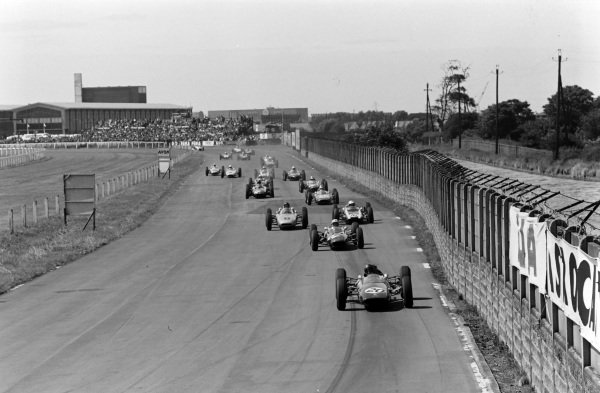 Jim Clark, Lotus 25 Climax, leads John Surtees, Lola 4 Climax, as Dan Gurney, Porsche 804, and Bruce McLaren, Cooper T60 Climax, battle at the start.