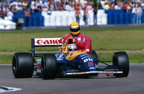 Race winner Nigel Mansell (GBR) Williams FW14 carries back to the pits fourth place finisher Ayrton Senna (BRA) McLaren, who ran out of fuel on the final lap. British Grand Prix, Silverstone, England, 14 July 1991.
