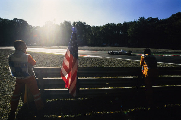 Jacques Villeneuve, BAR 003 Honda, drives past a pair of marshals. Between them, the stars and stripes flag of the United States. This race was the first since the 9/11 terror attacks on the World Trade Center in New York.