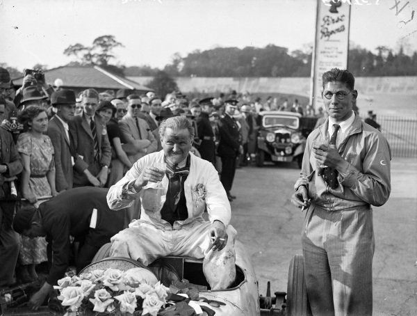 Freddie Dixon, 2nd position, sits on his Riley as Luis Fontes, 1st position, stands alongside.
