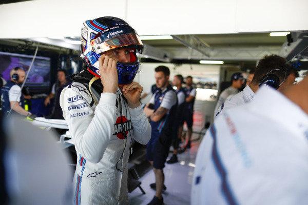 Sergey Sirotkin, Williams Racing, adjusts his helmet in the team's garage.