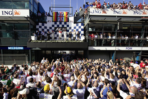The teams gather below to watch the podium ceremony.