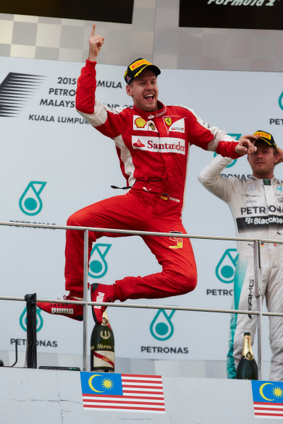 Sepang International Circuit, Sepang, Kuala Lumpur, Malaysia. Sunday 29 March 2015. Sebastian Vettel, Ferrari, 1st Position, leaps in celebration on the podium. World Copyright: Steve Etherington/LAT Photographic. ref: Digital Image SNE16343