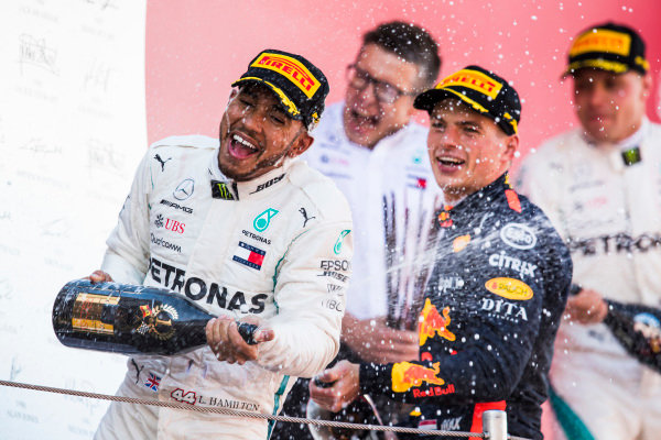 Lewis Hamilton, Mercedes AMG F1, 1st position, and Max Verstappen, Red Bull Racing, 3rd position, celebrate with Champagne on the podium.