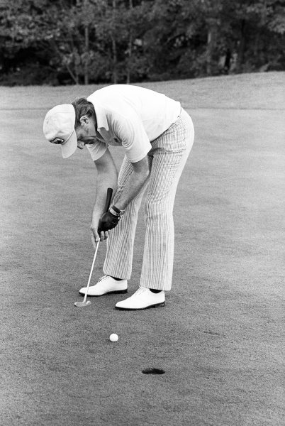 Graham Hill (GBR) Embassy Shadow, putts the ball towards the hole with an unfeasibly small putter during a pre race round of golf. United States Grand Prix, Rd 15, Watkins Glen, USA, 7 October 1973.