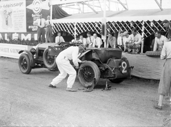 Frank Clement / Dick Watney, Team Bentley, Bentley Speed Six, working on the rear tyre in the pits as his team can only look on.